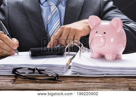 Midsection of businessman calculating invoice with piggy bank on documents at table