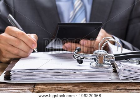 Midsection of businessman calculating invoice with stethoscope on documents at table