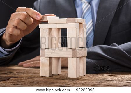 Midsection of businessman building tower with wooden blocks at table