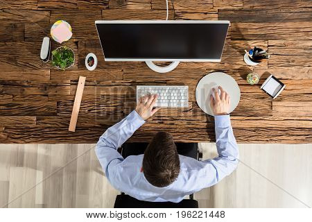 Close-up Of A Person Using Computer On Office Wooden Desk