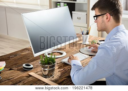 Businessman Using Computer With Black Screen In Office
