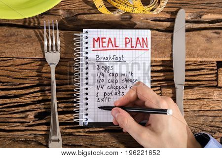 Elevated View Of Hand Making Meal Plan On Notebook With Fork And Knife On Desk