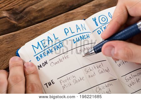 Elevated View Of A Human Hand Filling Meal Plan On Notebook At Workplace