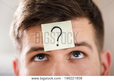Close-up Of A Businessperson's Forehead With Question Mark On Sticky Note