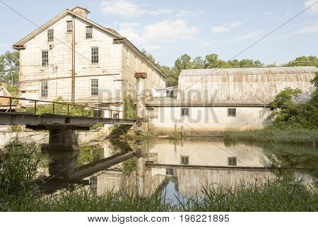 Wooden wool mill reflecting in stream against blue skies.