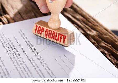 Close-up Of A Red Top Quality Stamp On Document Over Desk