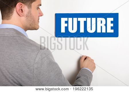 Close-up Of A Young Businessman Knocking White Door With Future Text