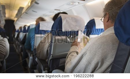 Aboard of aircraft. People are waiting for take-off. A man in glasses reading a magazine