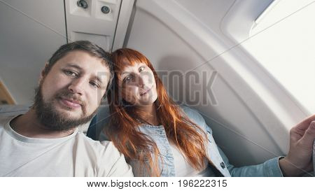 Portrait of a man couple - man and woman in the seat of aircraft in anticipation of take-off.