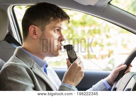 Close-up Of A Young Man Sitting Inside Car Taking Alcohol Test