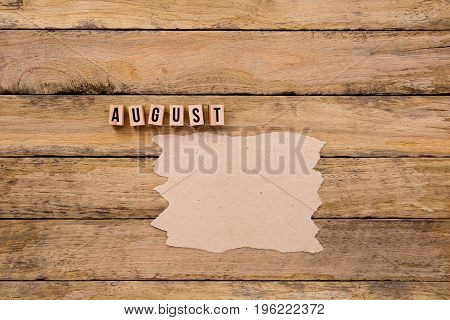 August - Calendar Month In Wooden Block Letters With Handmade Paper For Copy Space On Wooden Backgro