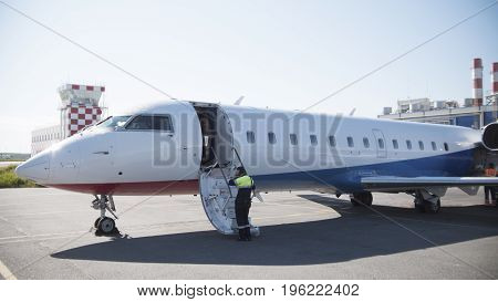 In an Airport. The airport employee rides aboard the aircraft to check