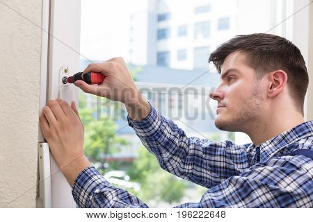 Male Handyman In Uniform Fixing Glass Window With Screwdriver