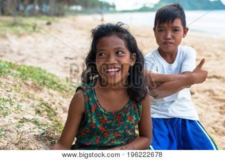 EL NIDO PALAWAN PHILIPPINES - JANUARY 20 2017: Local filipino girl smiling at Nacpan Beach. Behind her local boy posing to the camera.