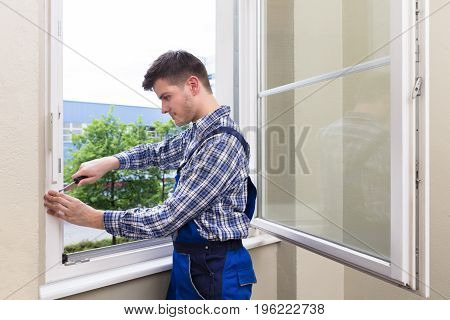 Close-up Of A Male Repairman Fixing Window With Screwdriver