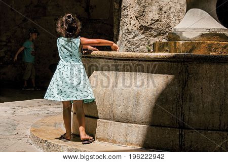 Saint-Paul-de-Vence, France - July 13, 2016. Alley with stone arches, children and fountain in Saint-Paul-de-Vence, stunning medieval village completely preserved. Provence region, southeastern France