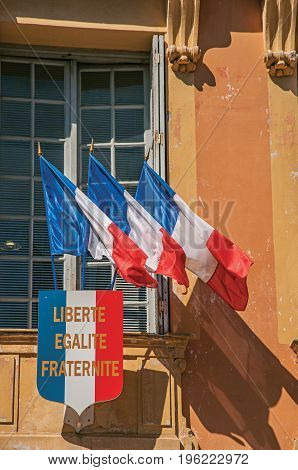 View of flags in the wind at the city hall's building of Vence, a stunning medieval hamlet completely preserved. Located in the Alpes-Maritimes department, Provence region, southeastern France