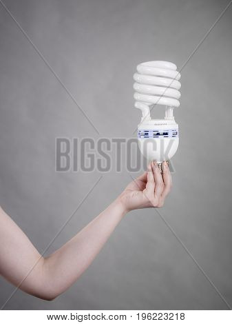 Woman hand holding eco modern light bulb. Innovation technology power saving concept.