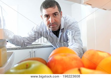 A man (age 40) looking for food to eat in the refrigerator. Healthy eating concept. Real people. Copy space.