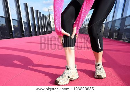 Woman having muscle cramp on bright pink cycleway road in Auckland New Zealand. Real people. Copy space.