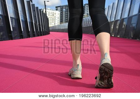 Womans Legs Walking On A Bright Pink Road
