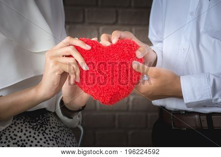 Red heart in woman and man hands, on brick wall background/ Male hand giving a red heart to a female hand