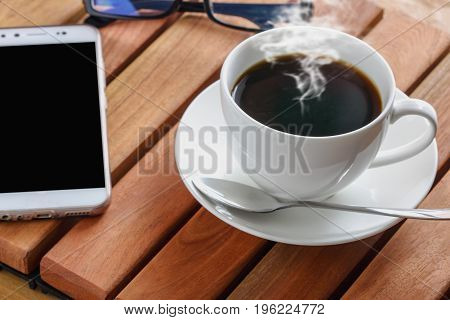 Coffee espresso cup hot with smart phone on a wooden tableReady to drink in the morning.