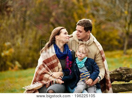 Portrait of cute loving family with little son in autumn park