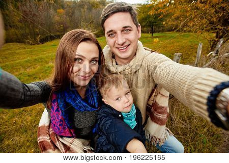 Cheerful smiling family making selfie in autumn forest