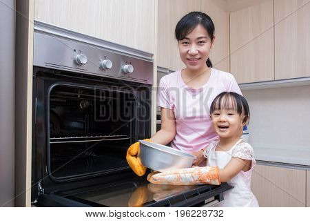 Asian Chinese Mother And Daughter Baking Cake Together