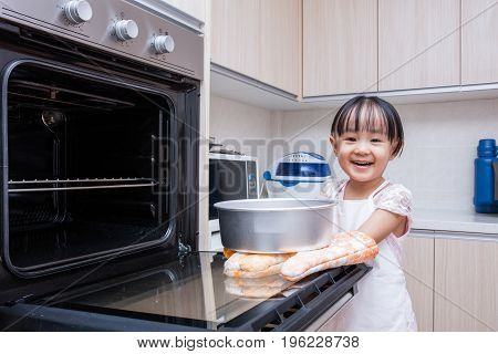 Asian Chinese little girl baking cake at home in the kitchen