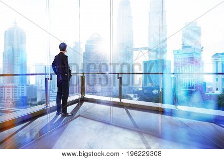 Young businessman looking out the city in the office . morning scene. .