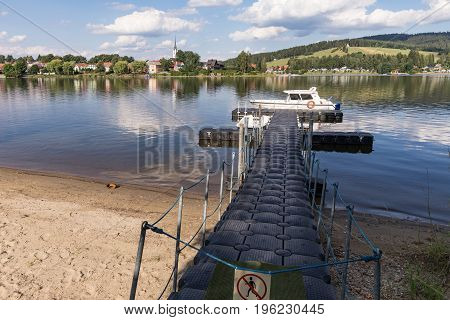 A barrel jet leading to the boat. Background view on village Frymburk Lipno lake Czech Republic. Frymburk in sunny day view from Frydava port.