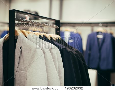 Close up view of man clothes hang in clothes store. Hangers with different male clothes. Copy space. Selective focus. Toned image