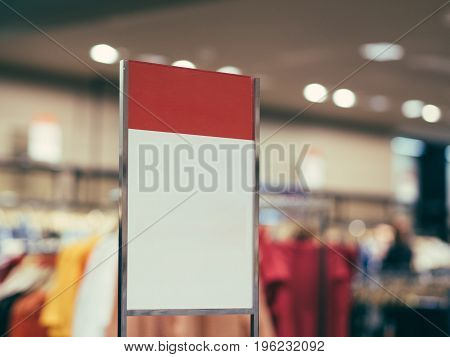 Red and white sign or label in clothing store as sale concept mock up. Shallow DOF. Copy space.