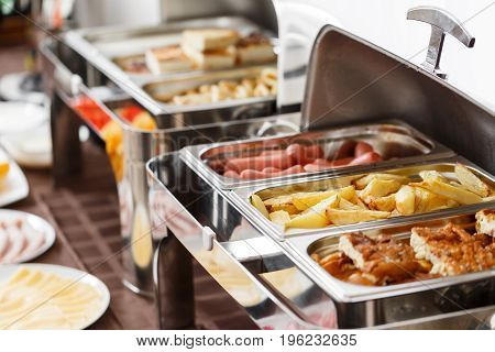 Breakfast at the hotel. fried potatoes and scrambled eggs and other hot dishes for Breakfast. Buffet Table with dishware waiting for guests. hot meals, vegetables, fruits, meats, cheeses. Coffee machine.