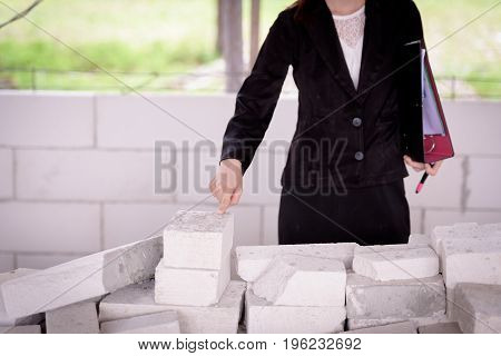 The Fingers Of A Businesswoman Pointing At A Brick In A Building Under Construction.