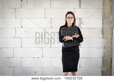Businesswoman Standing Holding A File  In A Brick Building.