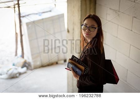 A Businesswoman Holds A Calculator While Walking Down A Stairwell In A Building Under Construction.