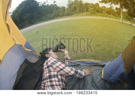 Beautiful smiling Asian woman lying down and looking Binoculars at the entrance of a blue - yellow camping tent.
