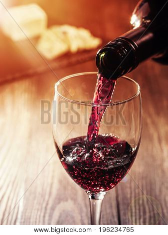 Closeup of red wine pouring in glass on wooden table. heese on background. Copy space. Sunflare effect