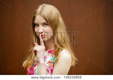 Young beautiful blonde woman has put forefinger to lips as sign of silence, against shop window
