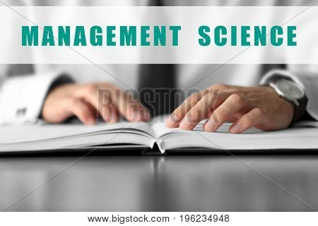 Concept of management science. Young man checking schedule in notebook, closeup