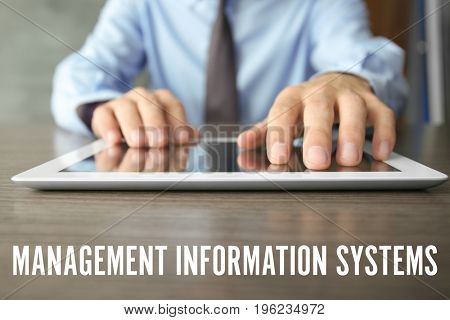 Concept of management information systems. Man using tablet at table, closeup