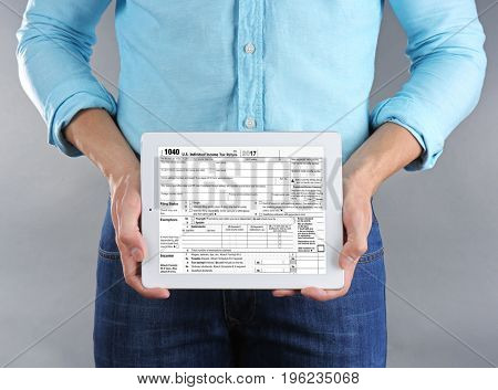 Man holding tablet with individual income tax return form on screen against grey background