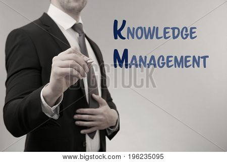 Concept of knowledge management. Businessman writing on virtual screen, closeup