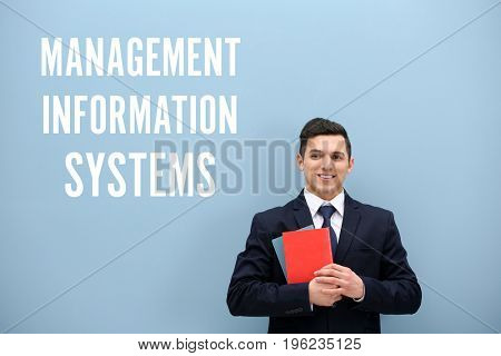 Concept of management information systems. Young man with books on color background
