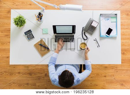 business, people and technology concept - businesswoman with laptop computer working at office and drinking coffee
