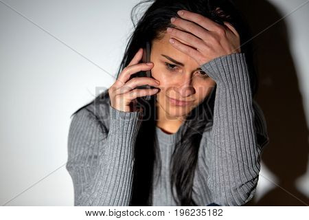 people, helpline and domestic violence concept - close up of unhappy woman crying and calling on smartphone