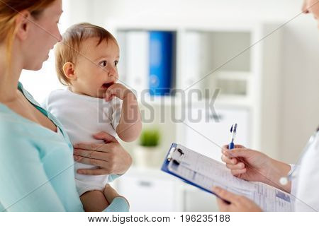 medicine, healthcare, pediatry and people concept - woman with baby and pediatrician or doctor with clipboard at clinic
